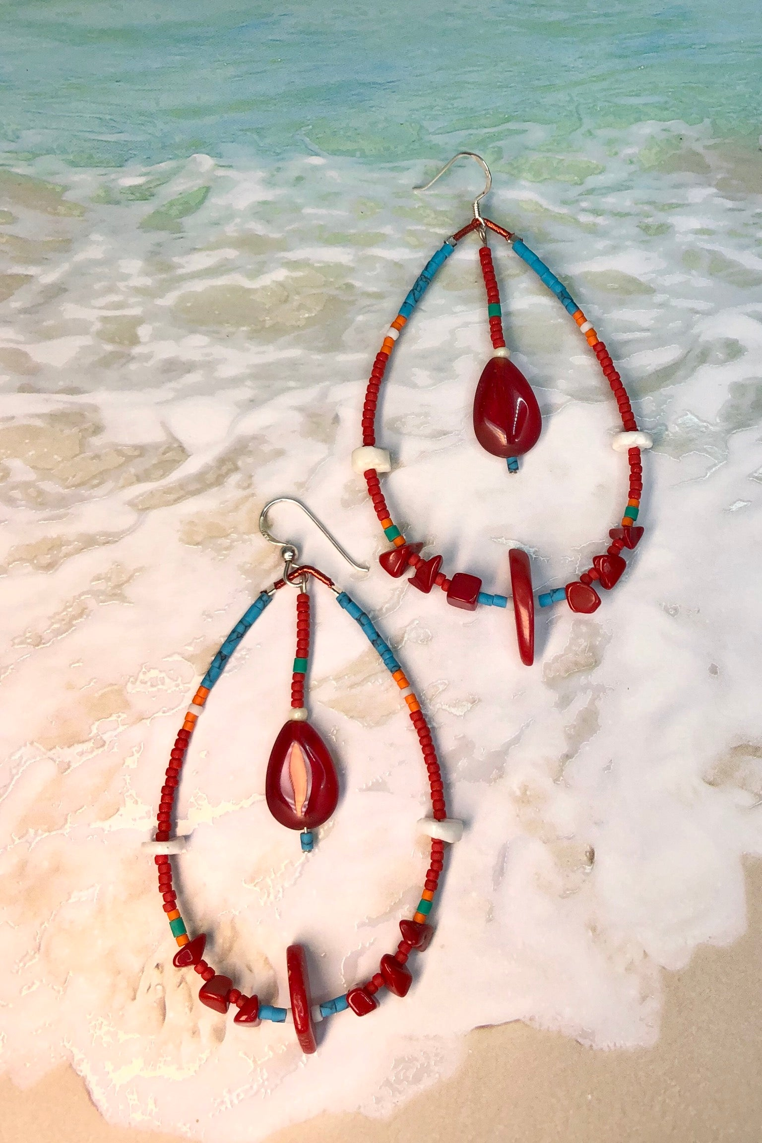 the handmade Earrings Cay Laguna Hoop Red feature seashells, crystal glass, red bamboo coral and sand beads.