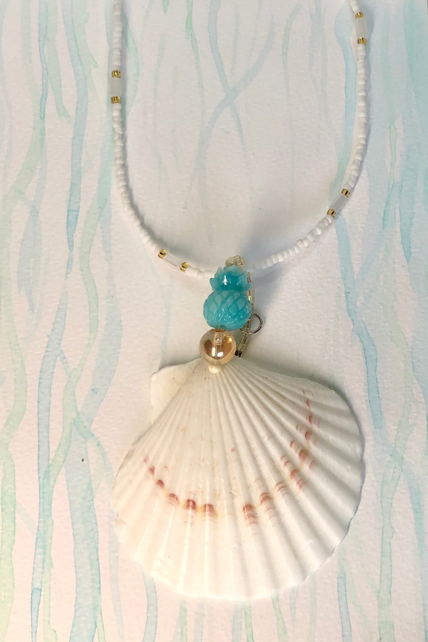 Swim in the cool Bahamas seas in the Pendant Cay Pineapple Ocean. A stunning sea shell necklace with an island vibe, in golden quartz,  and a pineapple.