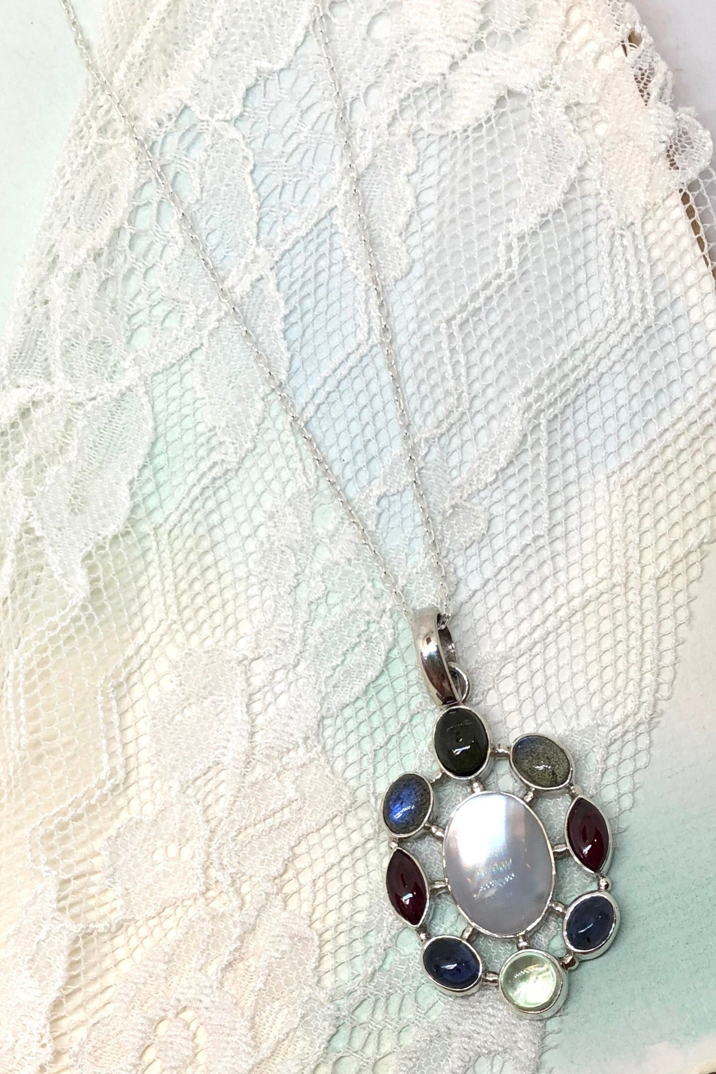 Echo Pendant Silver Gem Cosmos is a handmade pendant with Citrine, Tourmaline, Iolite around moonstone and comes on a 43 cm chain.