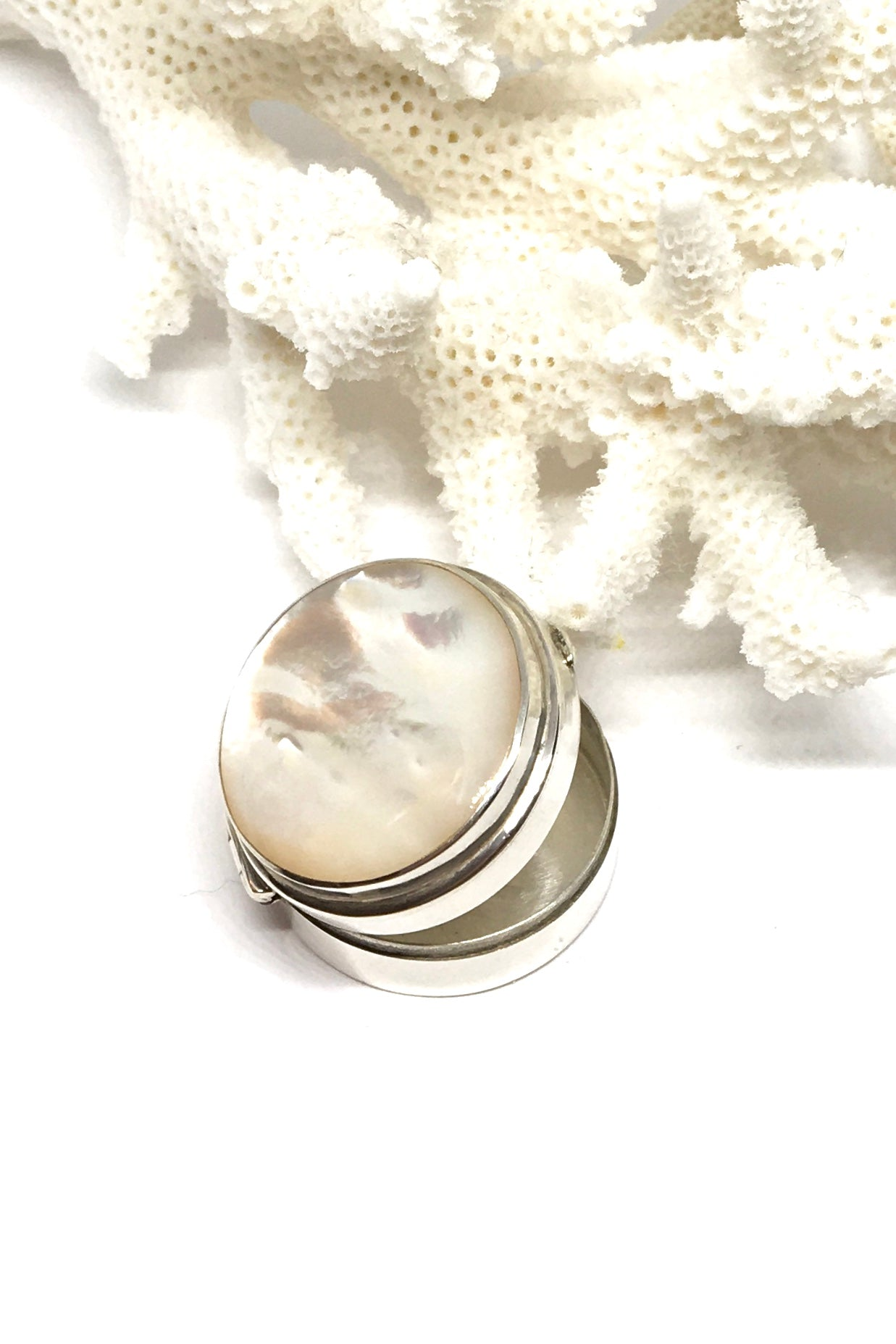shiny silver pill box inlaid with shimmery Mother of Pearl shell on the lid.