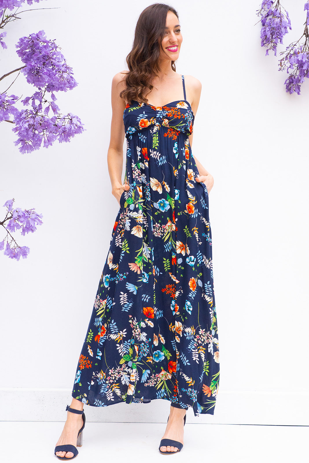 Emmy Clara Navy Maxi Dress features a flattering empire line with thin shoulder straps and side pockets in a bright navy floral print on woven 100% rayon