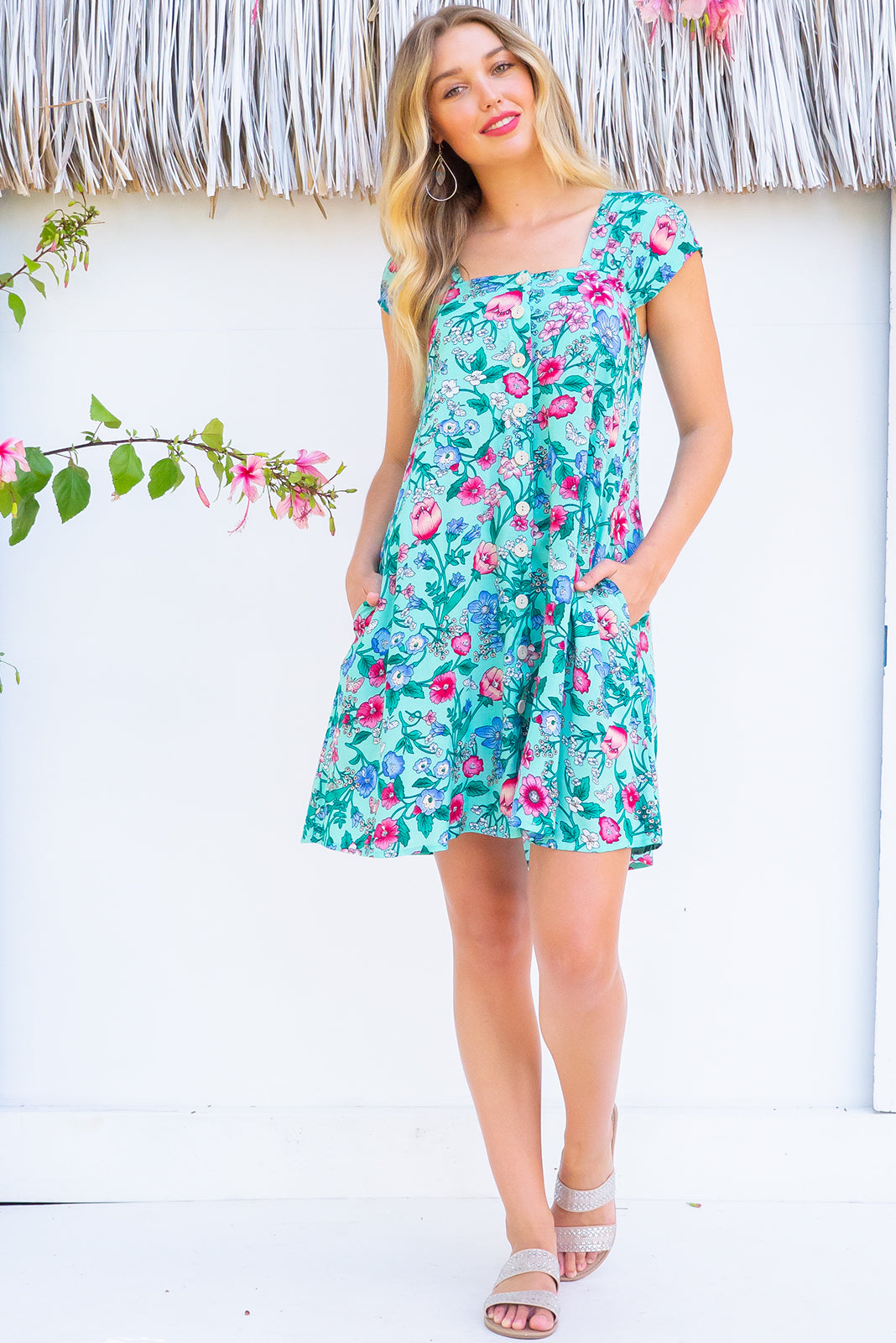 Etta Minty Meadow Dress with a gathered cap sleeve, full button front and deep side pockets comes with a self coloured belt and is made from a bright minty blue and floral  printed woven 100% rayon