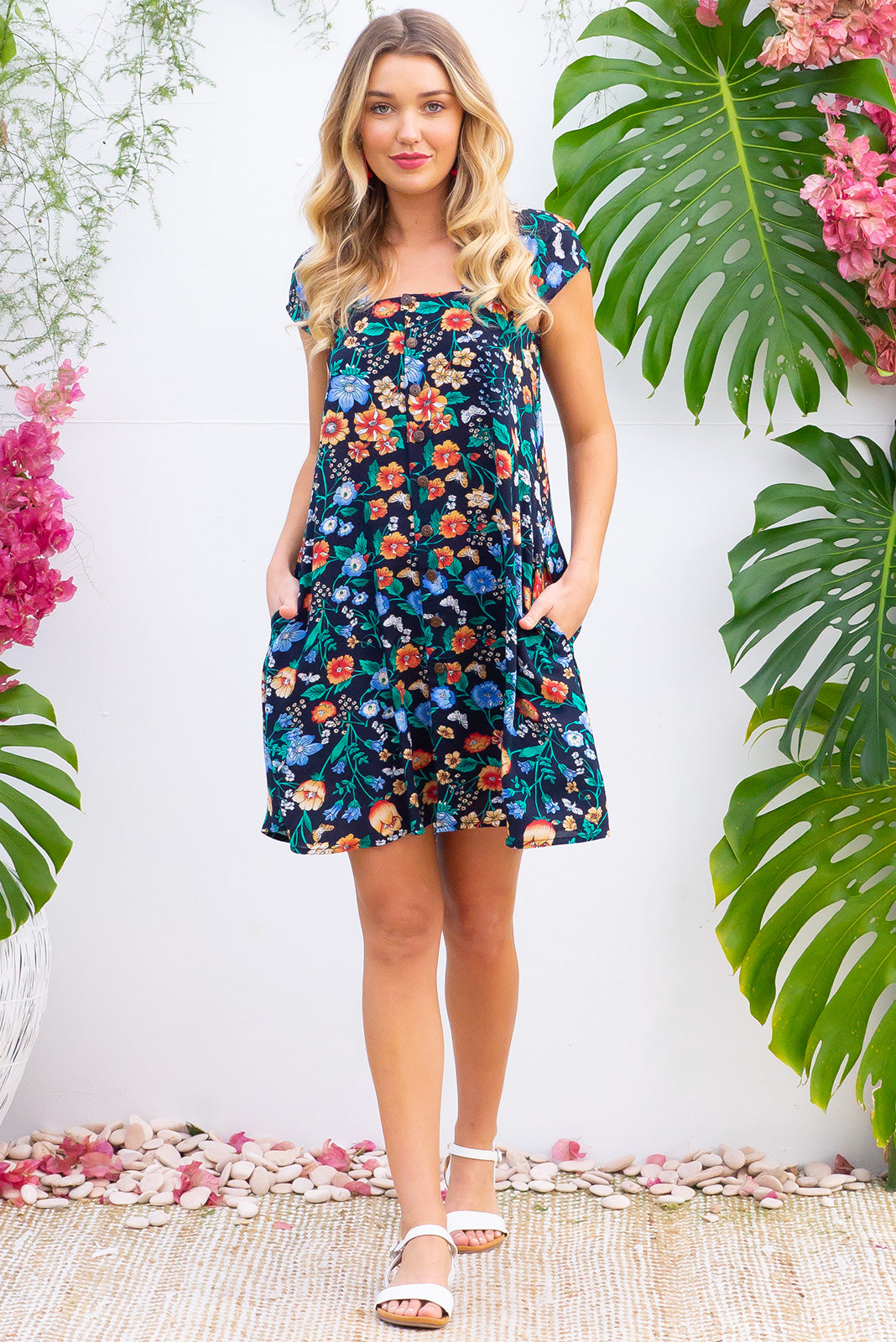 Etta Flight Navy Dress with a gathered cap sleeve, full button front and deep side pockets comes with a self coloured belt and is made from a dark navy and bright floral printed woven 100% rayon