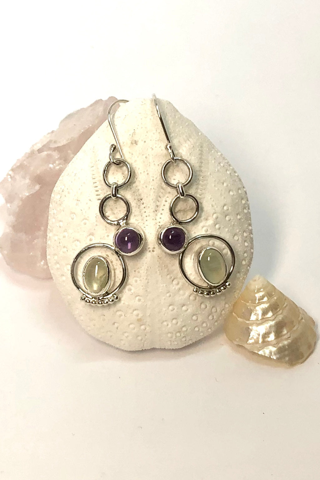 The Earrings Hoopla Circles pair feature a pale purple Amethyst and Moonstone gemstone set in uneven descending circles.