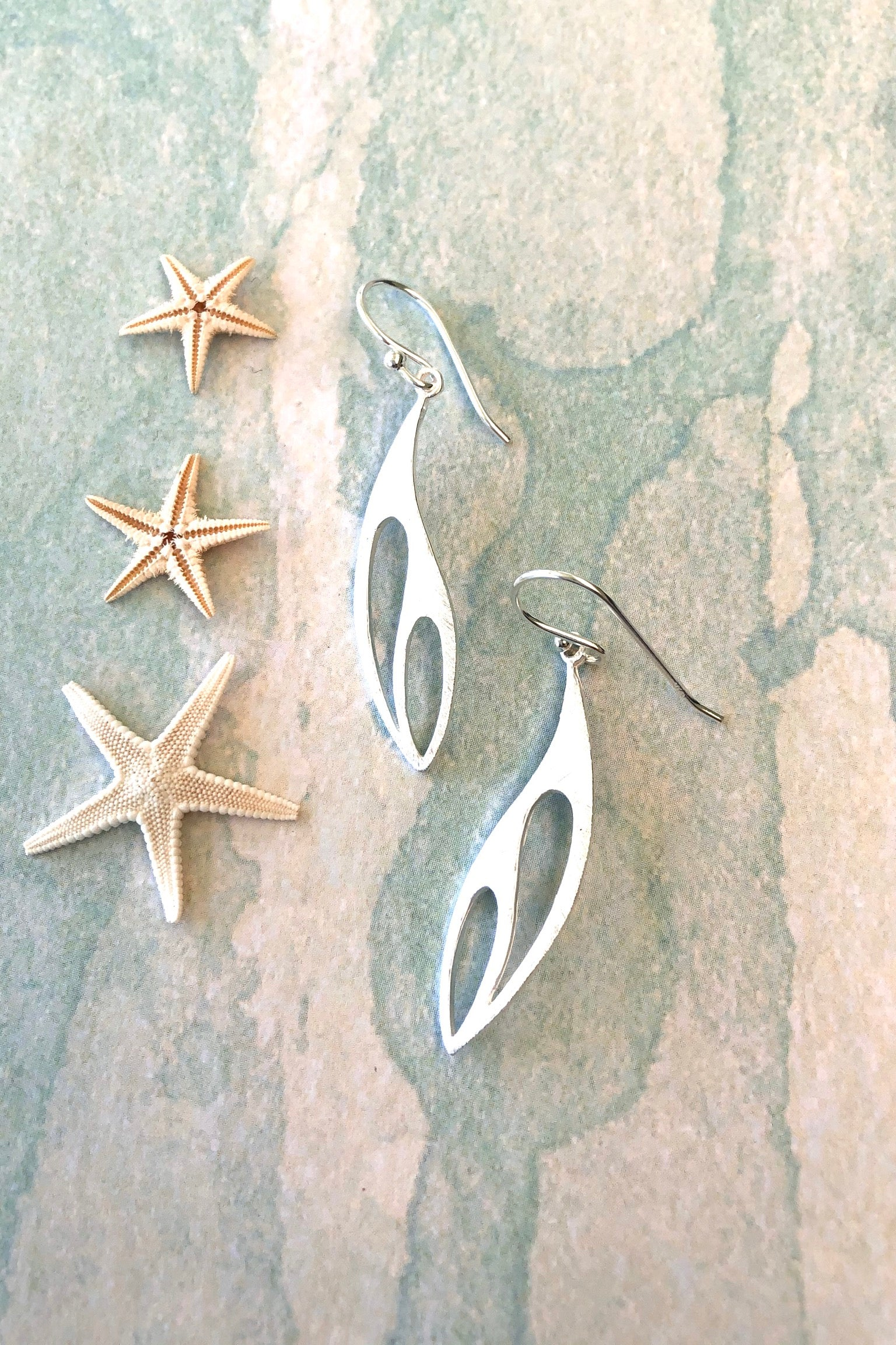 Fine silver drop earrings with an other-worldy curved shaped and hollow centre