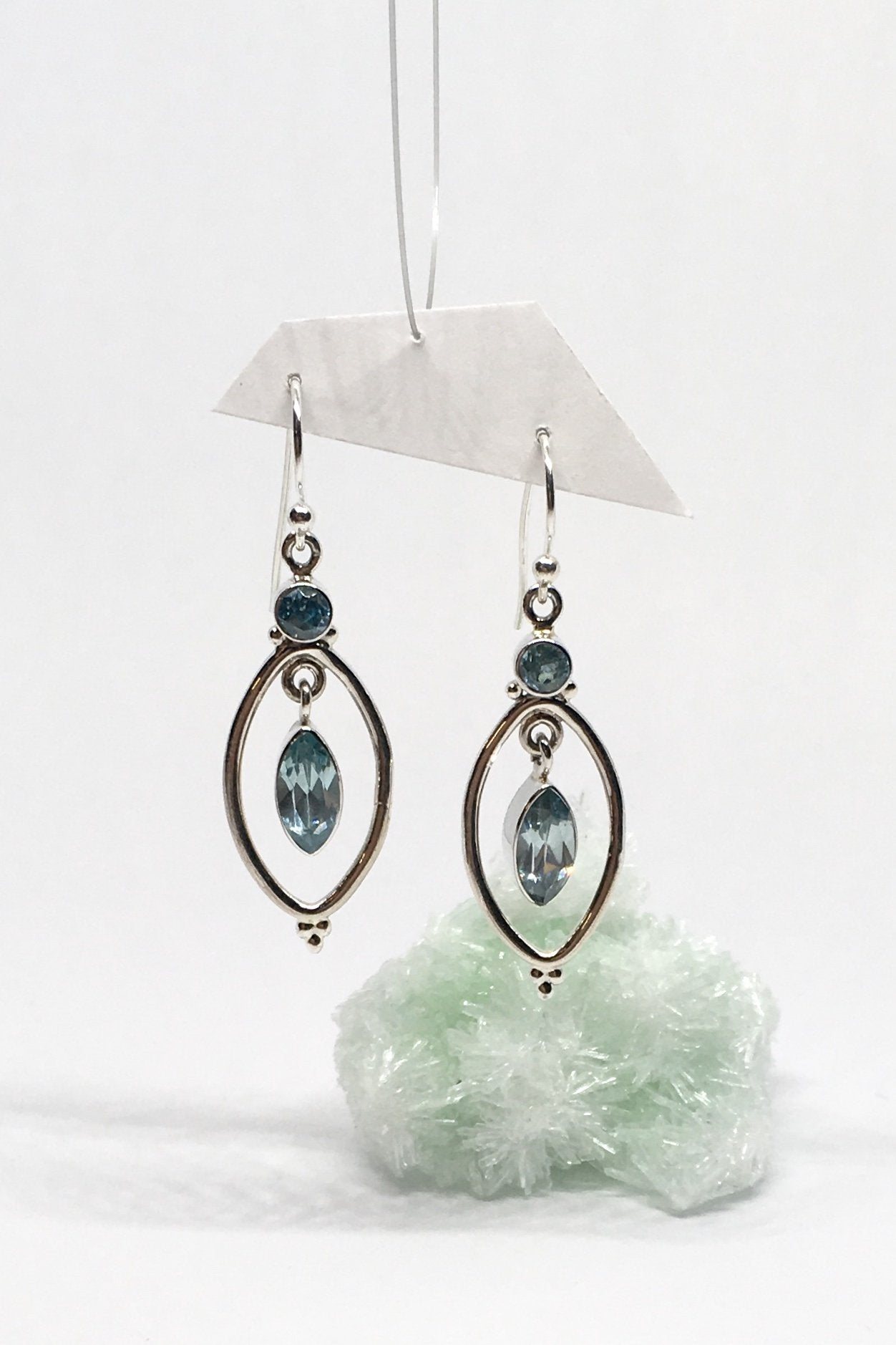A beautiful dainty earring in 925 silver, this design features a hanging oval faceted gemstone, with a circlet of silver