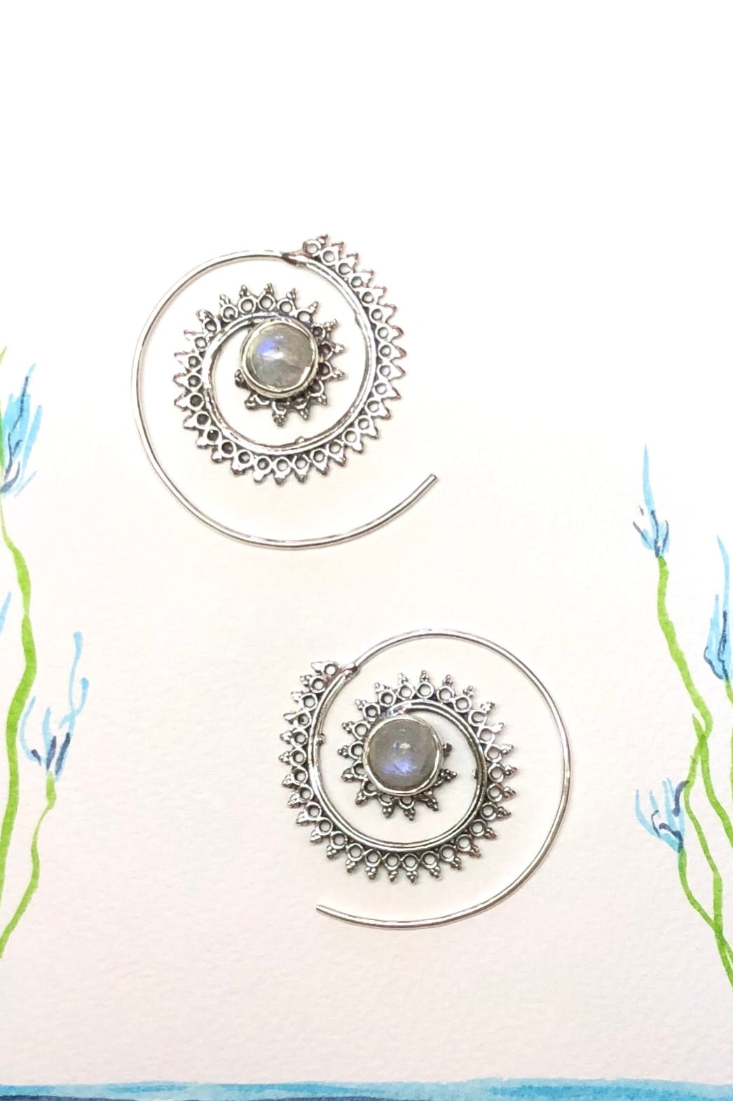 An iridescent moonstone sits at the centre of these unique silver swirl hoops.