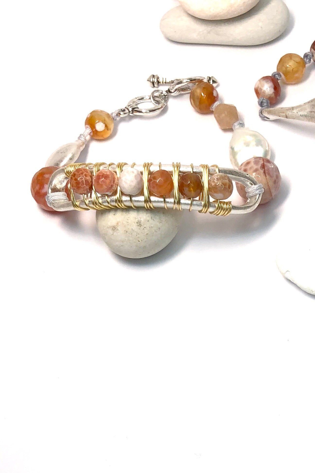 The Pebble Carnelian Arch bracelet has a rustic earth vibe featuring natural Carnelian gemstone, T-bar closure and white metal.
