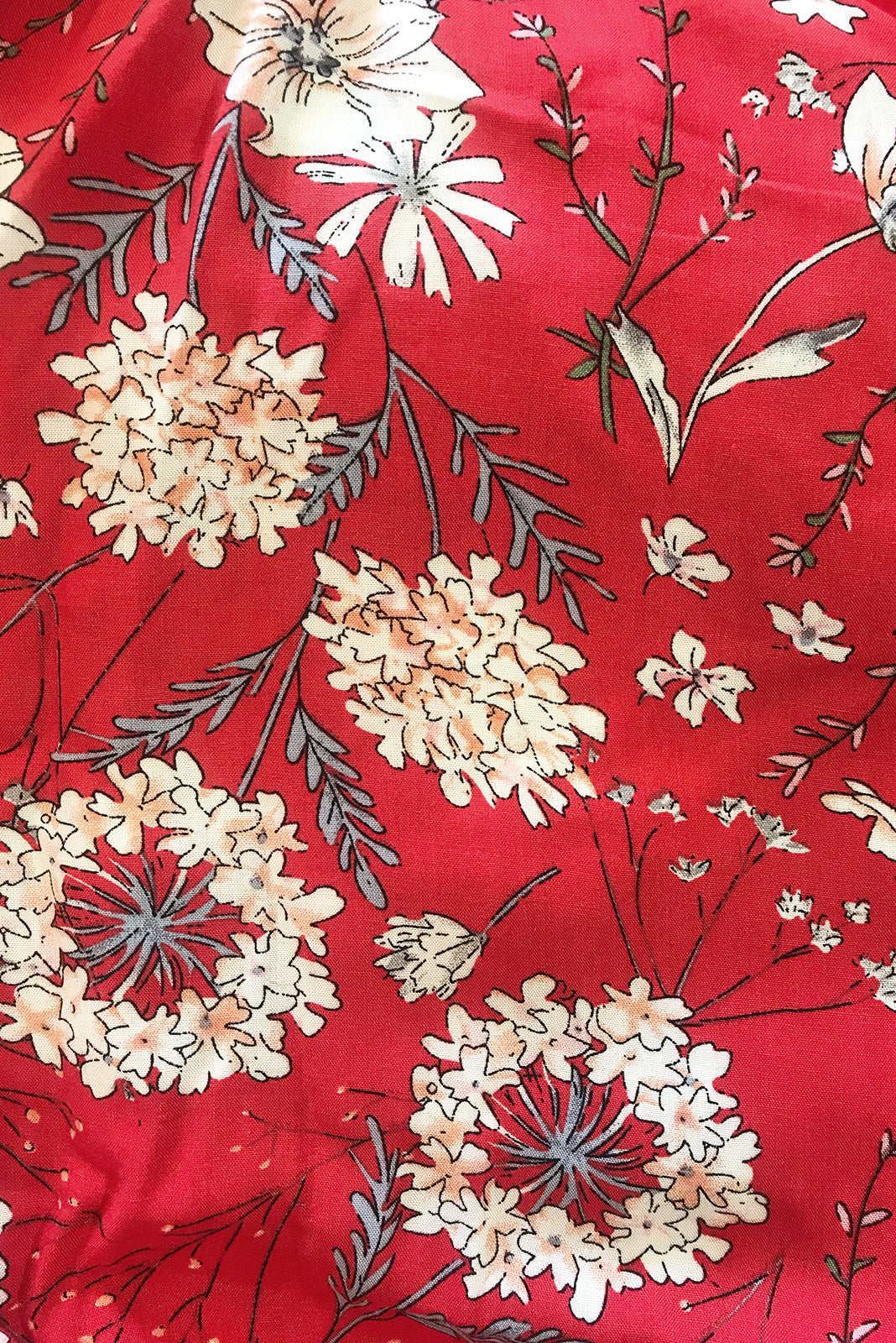 Fabric swatch, 100% woven rayon, bright red base with large cream, gold and soft sage floral print.