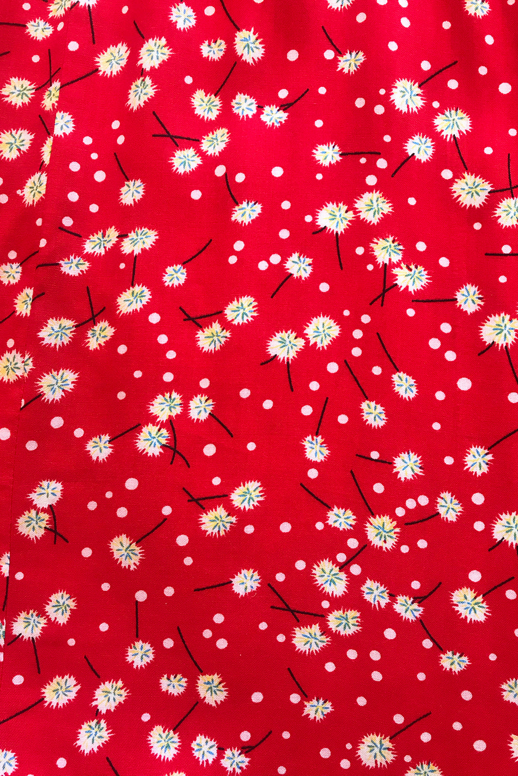 Fabric swatch, 100% woven viscose, bright red base with petite white, forest green and black dandelion floral print.