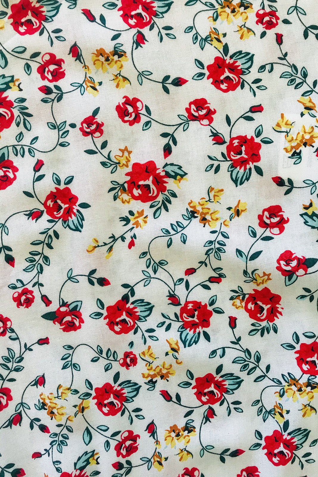 Fabric swatch, 100% woven viscose, white base with petite red, yellow and forest green rose floral print.