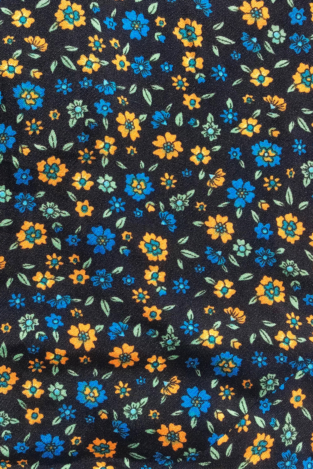 Fabric swatch, 100% rayon, black base with petite gold, bright blue and mint floral pattern.