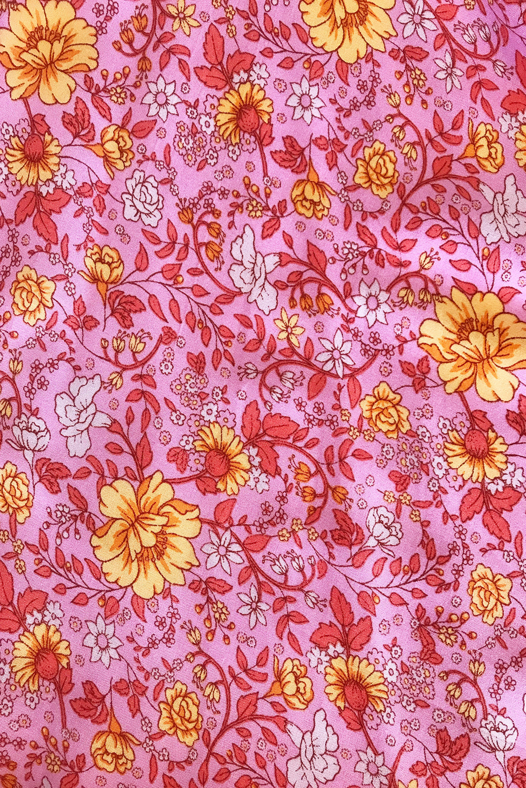 Fabric swatch, 100% woven viscose, bright pink base with medium gold, orange, soft pink and coral floral print.