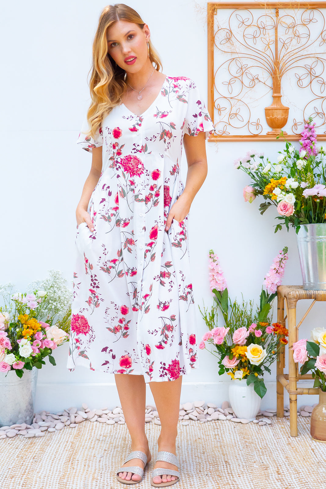 Faithful Lilly White Midi dress features a button front, soft petal sleeve and deep side pockets it is made in a crinkled woven rayon and comes in a crisp white and pink floral