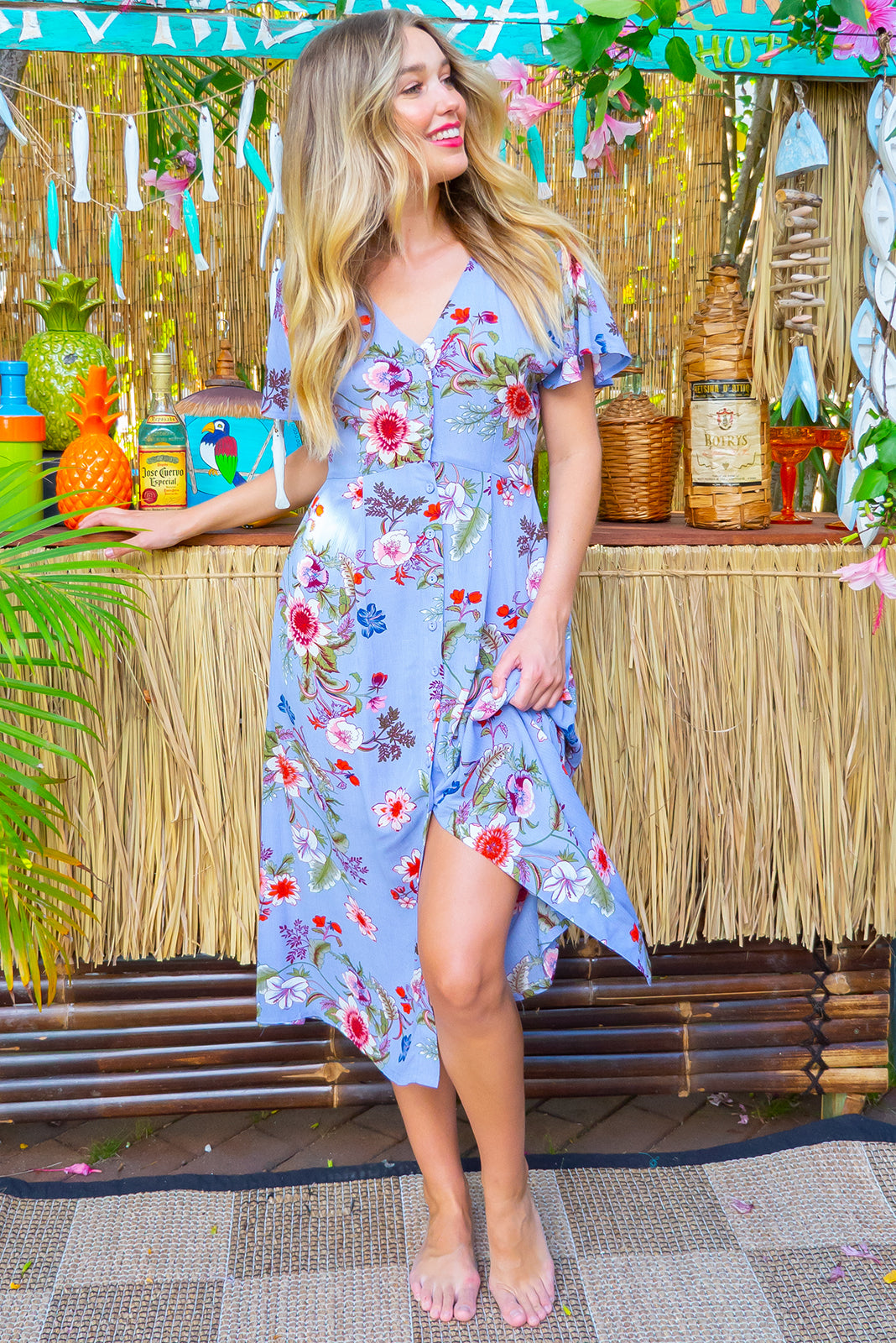 Faithful Maya Blue Midi dress features a button front, soft petal sleeve and deep side pockets it is made in a crinkled woven rayon and comes in a soft periwinkle blue with a floral print