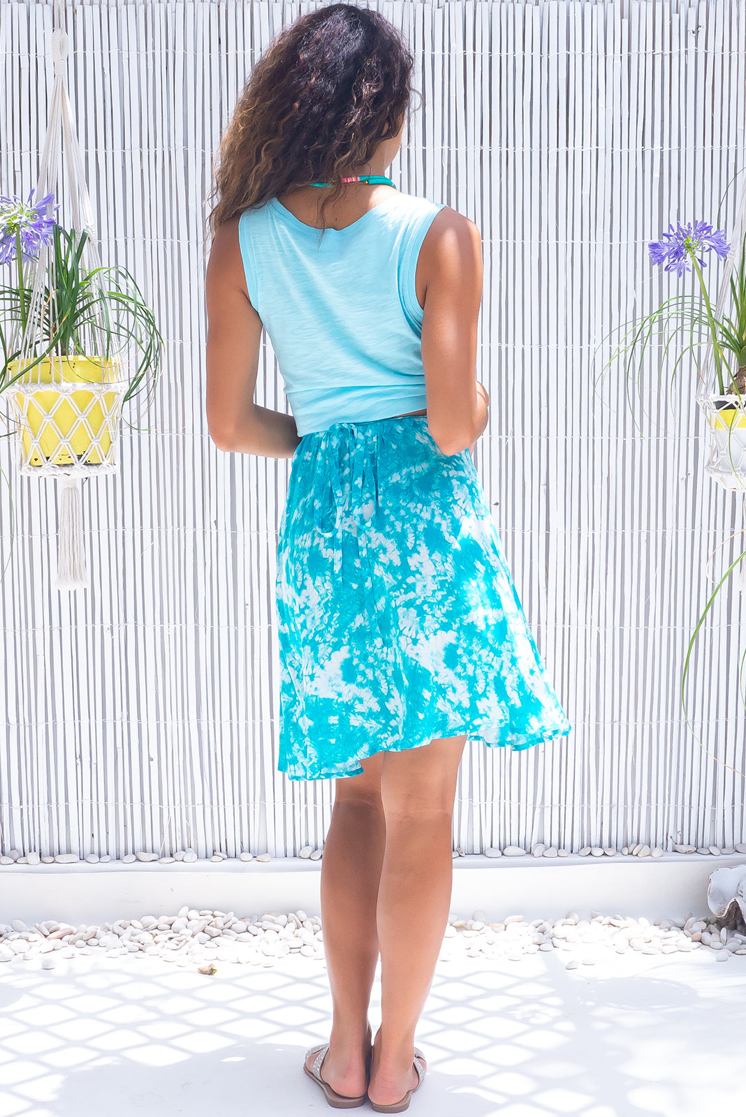 The Flamingo Lagoon blue Wrap Skirt features tie waist, elasticated back of waist, side pockets and 100% viscose in turquoise and white tie dye print.