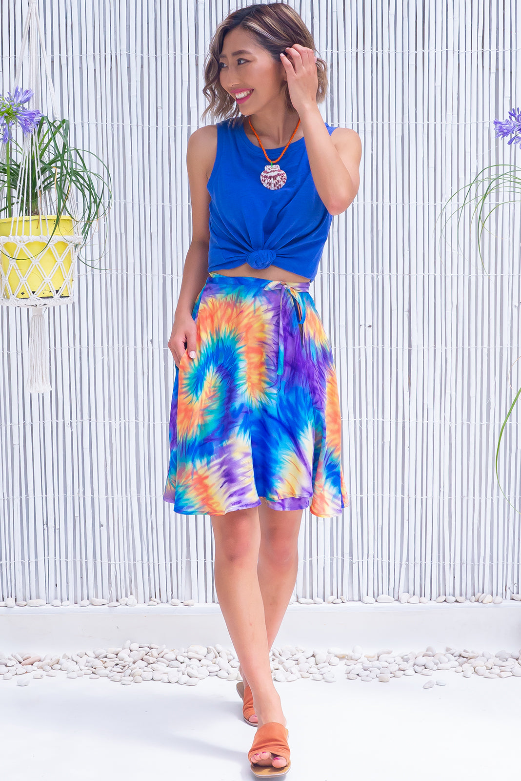 The Flamingo Party Time Wrap Skirt is a wrap around design skirt featuring elasticated back of waist, side pockets and woven 100% viscose in cobalt, purple, yellow, orange fireworks/tie dye effect.
