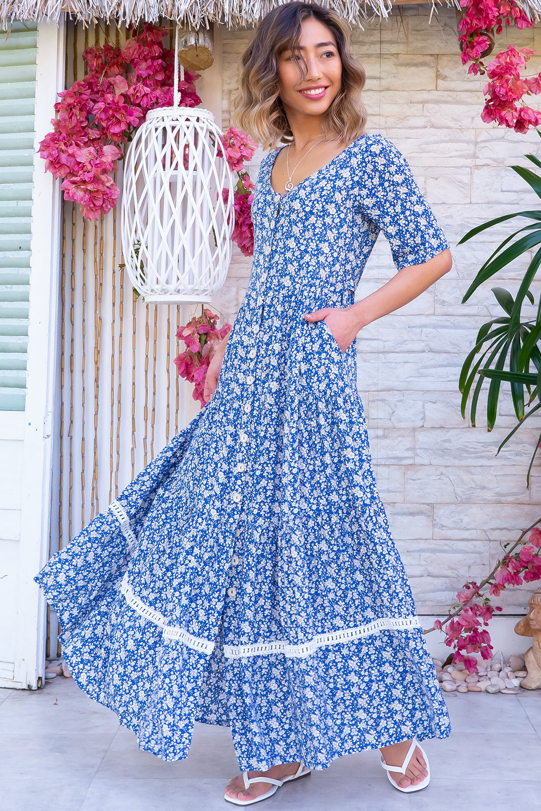 The Georgiana Blue Jay Maxi Dress features functional button front, buttons and side tabs at waist, side pockets, tiered skirt with lace insert and 100% rayon in blue base with white daisy print.