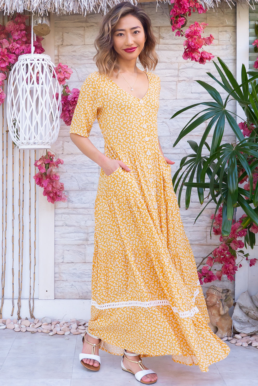 The Georgiana Gold Lark Maxi Dress features functional button front, buttons and side tabs at waist, side pockets, tiered skirt with lace insert and 100% rayon in gold base with delicate white floral design.