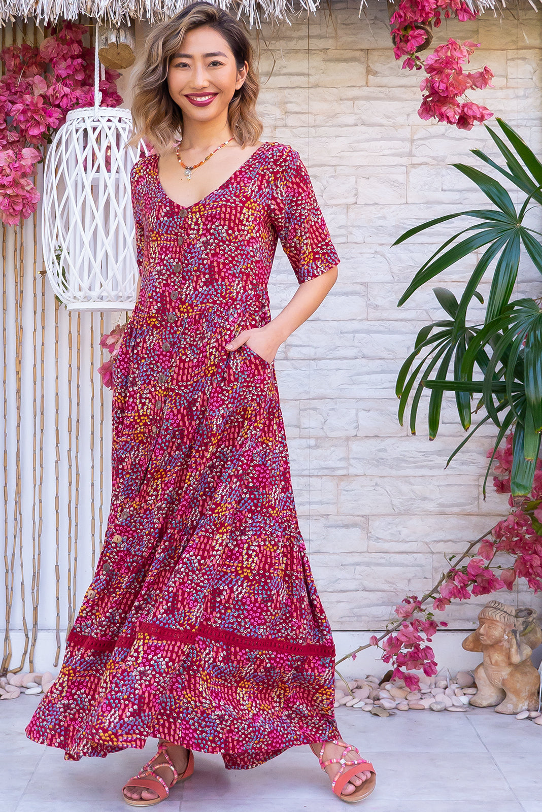 Georgiana Lah De Dah Red Maxi Dress features functional button front, buttons and side tabs at waist, side pockets, tiered skirt with lace insert and 100% rayon in deep red base with colourful confetti floral design.