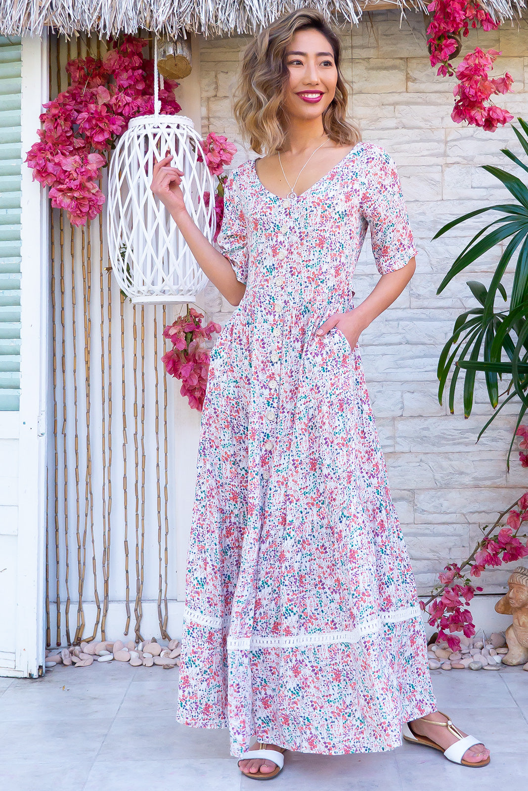 The Georgiana Field Flowers White Maxi Dress features functional button front, buttons and side tabs at waist, side pocket, tiered skirt with lace insert and 100% rayon in white base with sweet floral print.