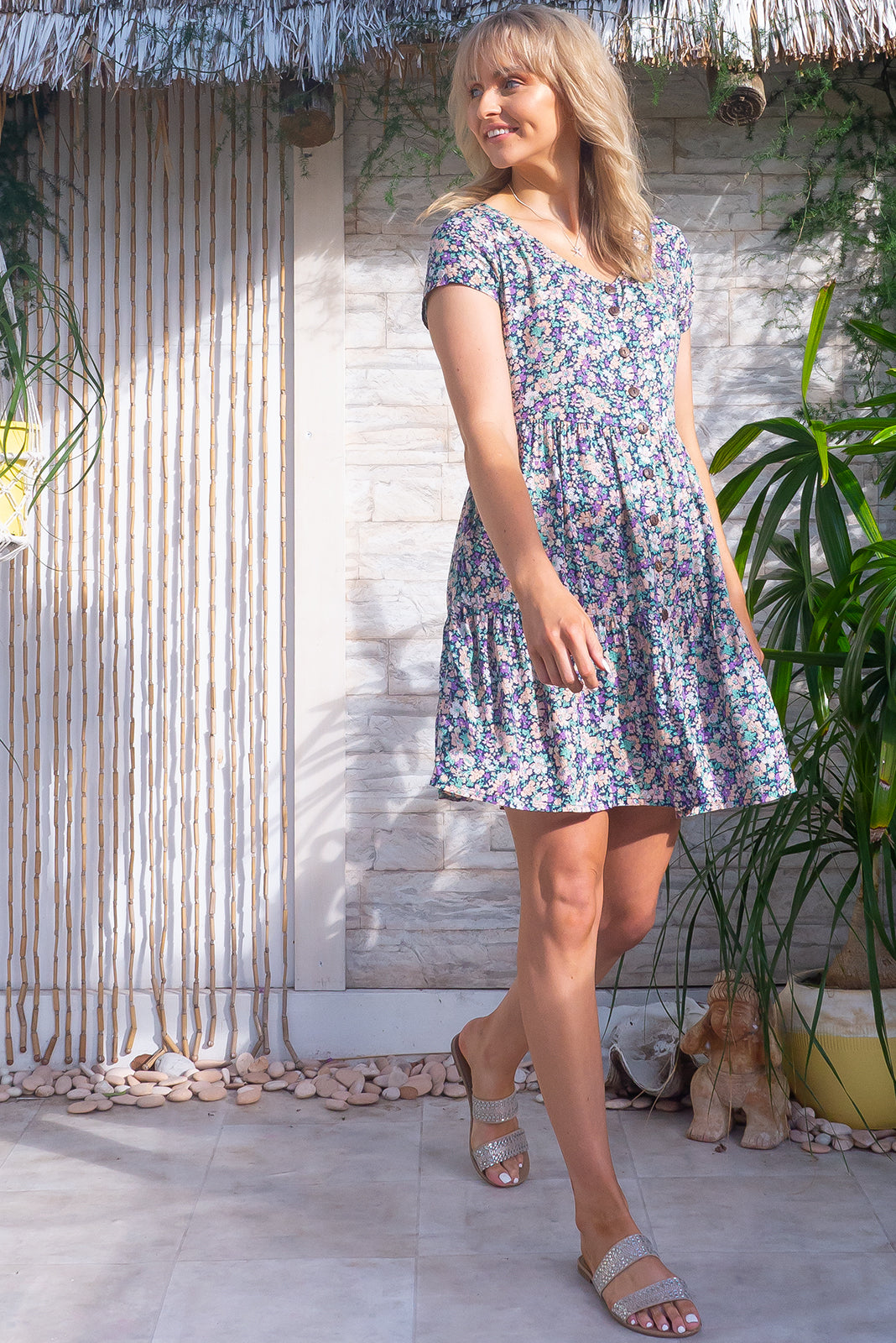 The Georgie Country Mauve Dress features functional button front, cap sleeves, adjustable side tabs, side pockets, frilled hem and 100% rayon in navy base with pink, purple and white floral print.