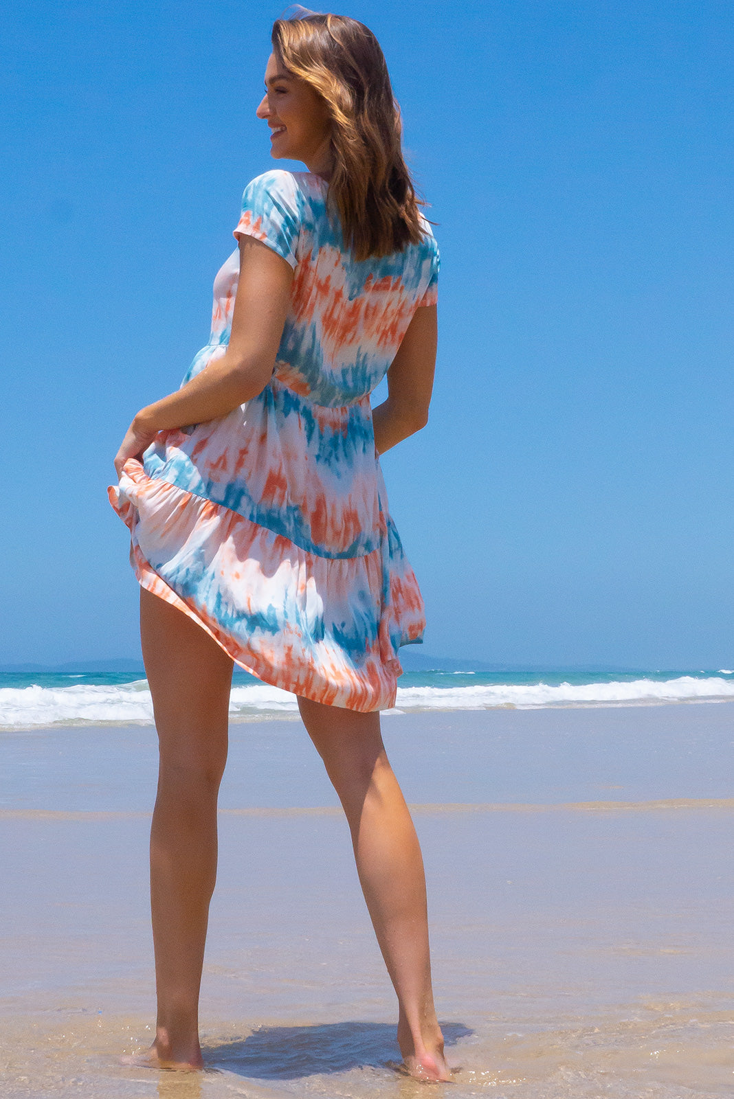 The Georgie Earth and Sea Dress features functional button front, cap sleeves, adjustable side tabs, side pockets, frilled hem and 100% rayon in blue, rust and white tie dye.