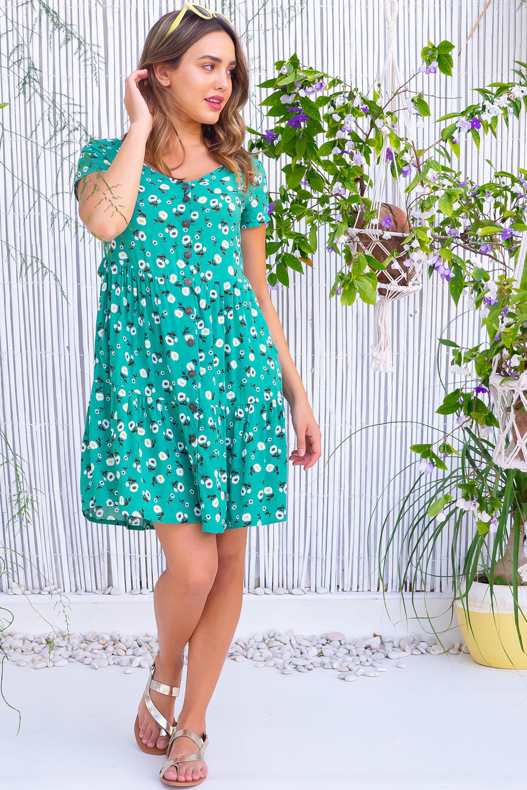 The Georgie Jade Garden Dress features functional button front, adjustable side tabs, side pockets, frilled hem and 100% rayon in green base with floral print.