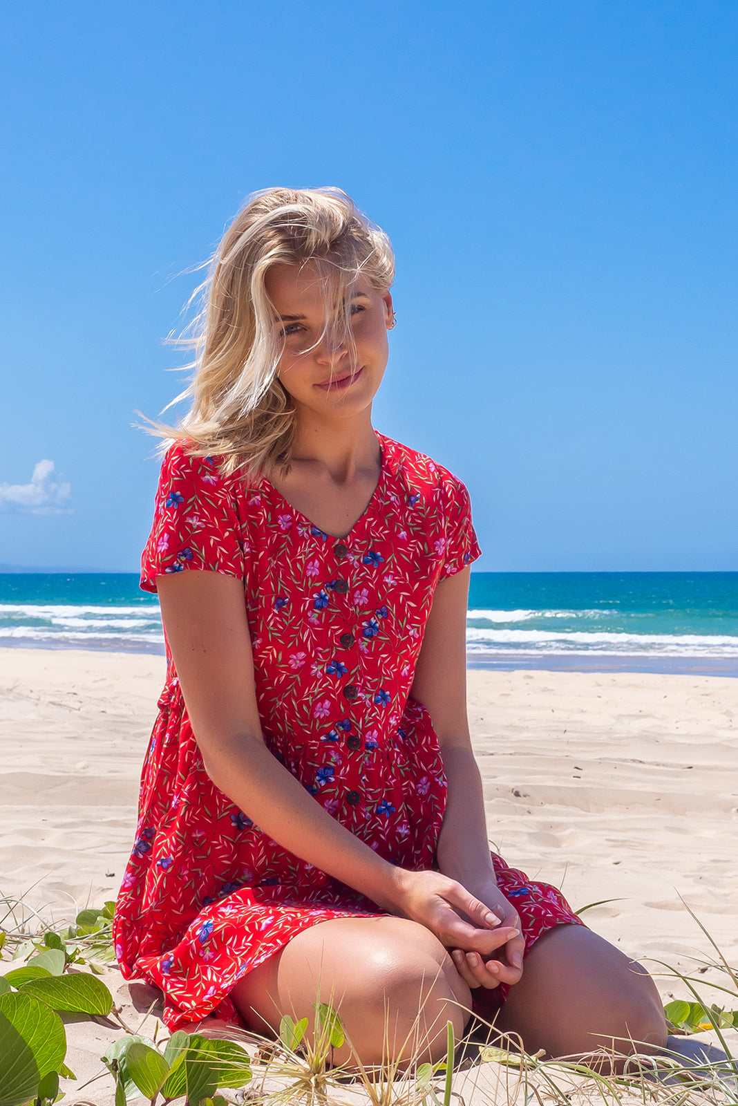 The Georgie Rosso red Dress features functional button front, adjustable side tabs, side pockets, frilled hem and 100% rayon in red base with floral print.