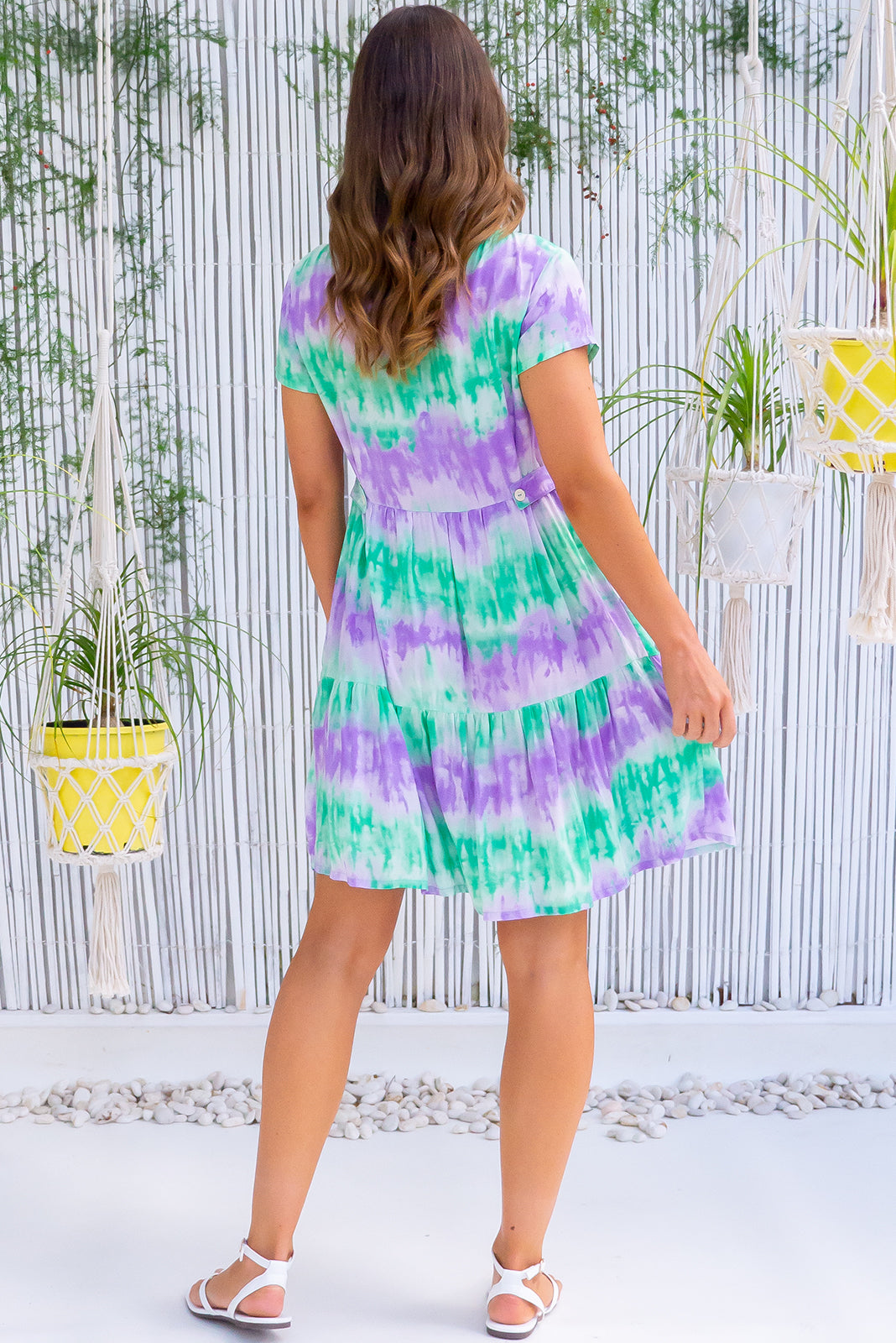 The Georgie Tie Dye Fun Dress features functional button front, cap sleeves, adjustable side tabs, side pockets, frilled hem and 100% rayon in sherbet tones of purple and green tie dye.