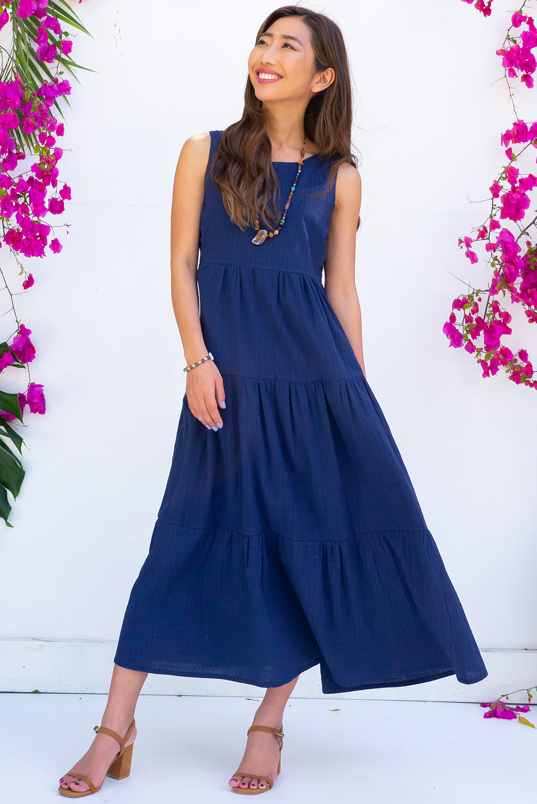 The Goldie Inky Navy Midi Dress is made from 100% cotton and features a tiered skirt and side pockets.