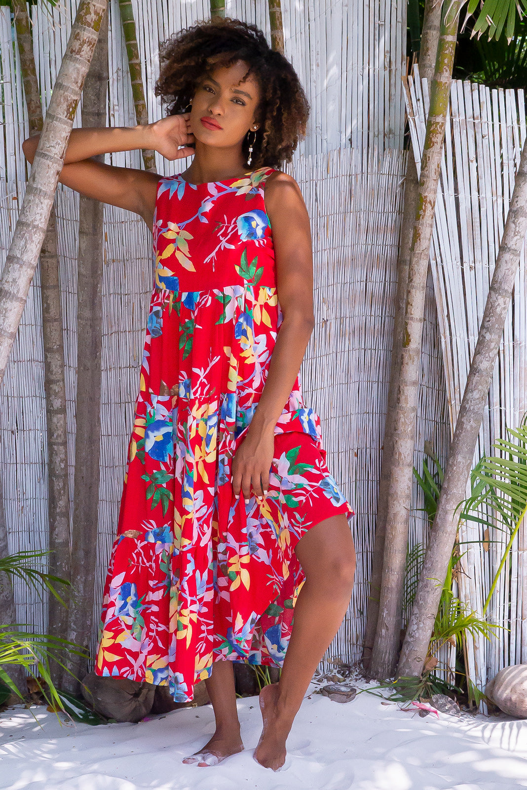 Goldie Red Reflections Dress, bohemian summer style, 100% cotton, high scooped neckline, sleeveless, three tiered skirt, side pockets, bright red base with large yellow, blue, green and white floral and palm print.