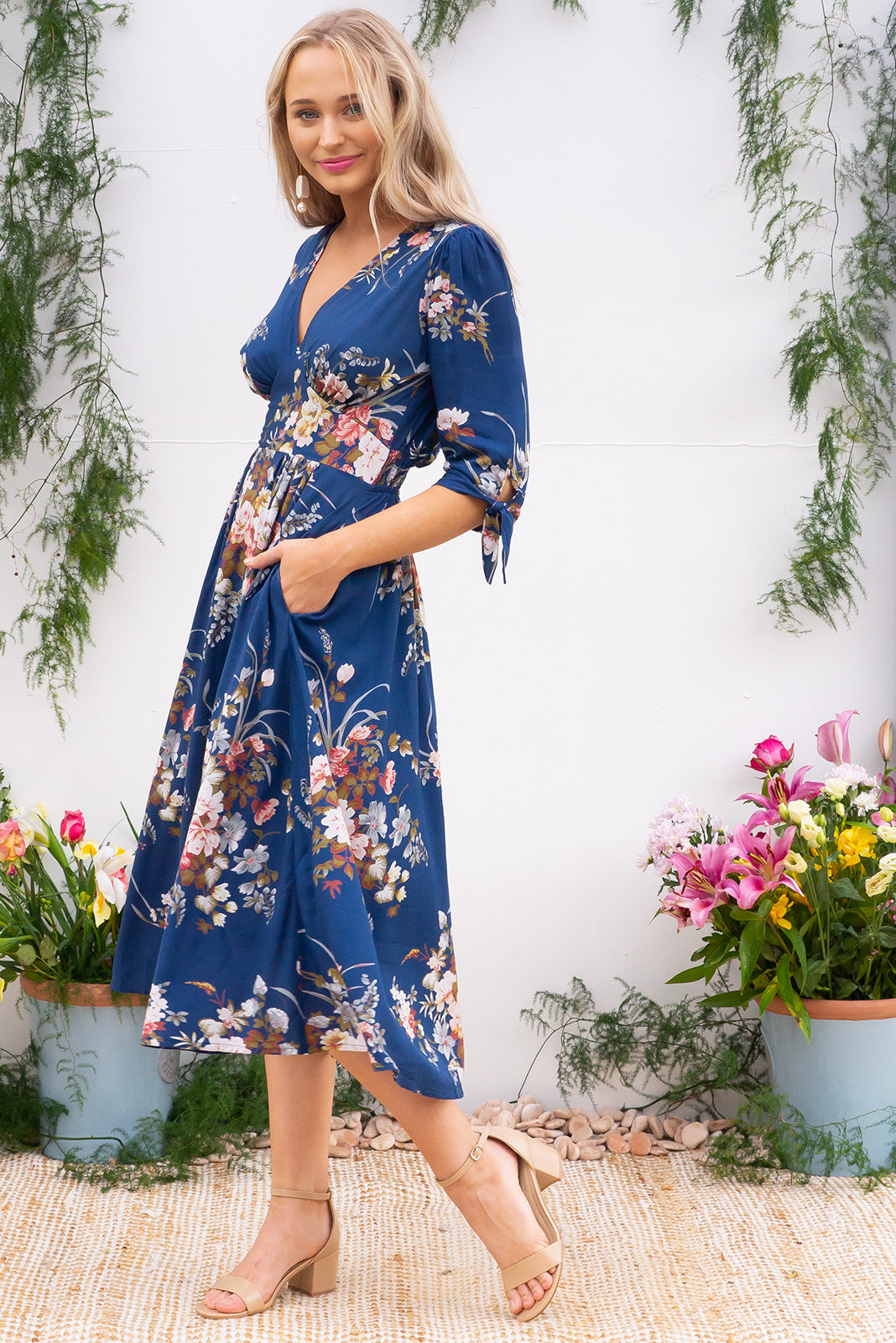 Henrietta Navy Bouquet Midi dress features a vintage inspired fitted basque waist and elasticated waist with a midi sleeve and deep v neck the fabric is a soft woven rayon in a soft romantic navy bouquet floral print