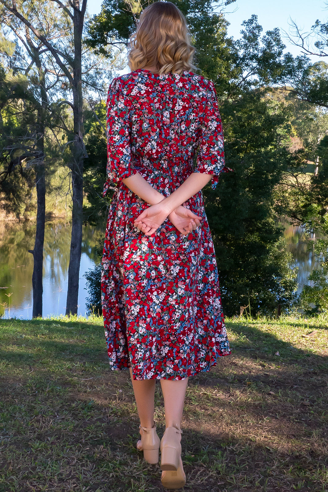 Henrietta Red Yves Dress features 3/4 tie sleeves, fitted basque waist with gathered bust, waist back elasticated, side pockets and woven 100% rayon in black base with a confetti floral print in red, pink, blue, green and white.