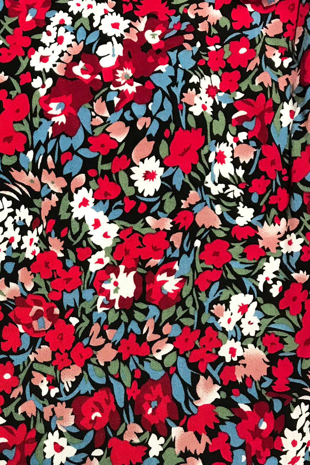 Fabric swatch of Henrietta Red Yves Dress featuring woven 100% rayon in black base with a confetti floral print in red, pink, blue, green and white.