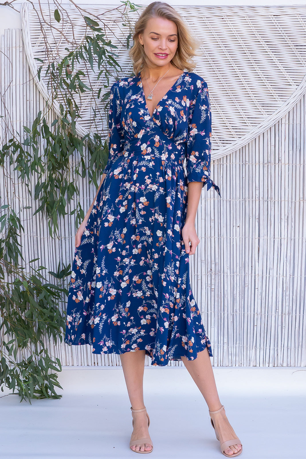 Henrietta Wildflowers Navy Dress is made of woven 100% rayon in   Navy base with a romantic pink, red and blue floral print and features 3/4 tie sleeves, fitted basque waist with gathered bust, waist back elasticated and Side pockets.
