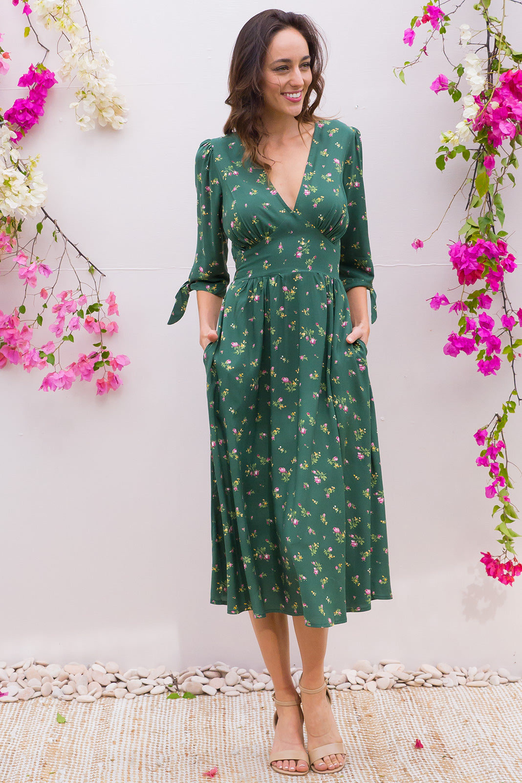 Henrietta Greenhouse Midi dress features a vintage inspired fitted basque waist and elasticated waist with a midi sleeve and deep v neck the fabric is a soft woven rayon in a dusty green delicate floral print