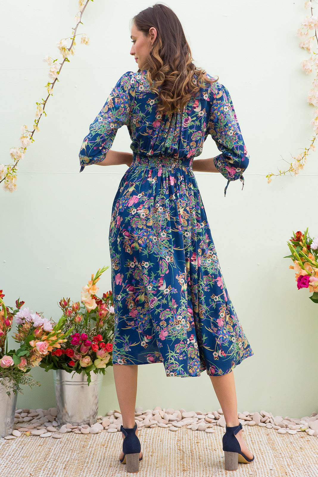 Henrietta Honey Eater Navy Midi dress features a vintage inspired fitted basque waist and elasticated waist with a midi sleeve and deep v neck the fabric is a soft woven rayon in a soft navy intricate bird and floral print