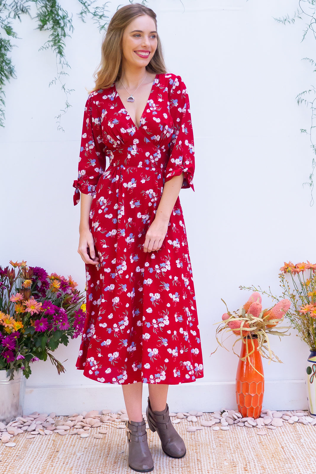 Henrietta Sangria Red Midi dress features a vintage inspired fitted basque waist and elasticated waist with a midi sleeve and deep v neck the fabric is a soft woven rayon in a strong bright red bohemian ditzy floral print