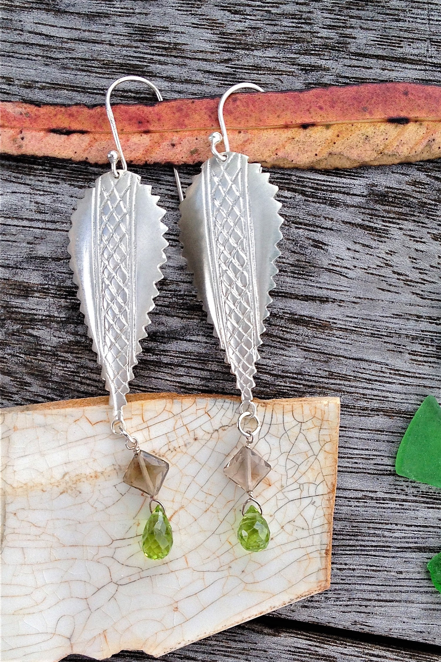 The African inspired design of these earrings was obtained by casting a pair of Mozambique Ebony wood earrings in silver. A Peridot gemstone briolet and a faceted smoky quartz hang from the base.