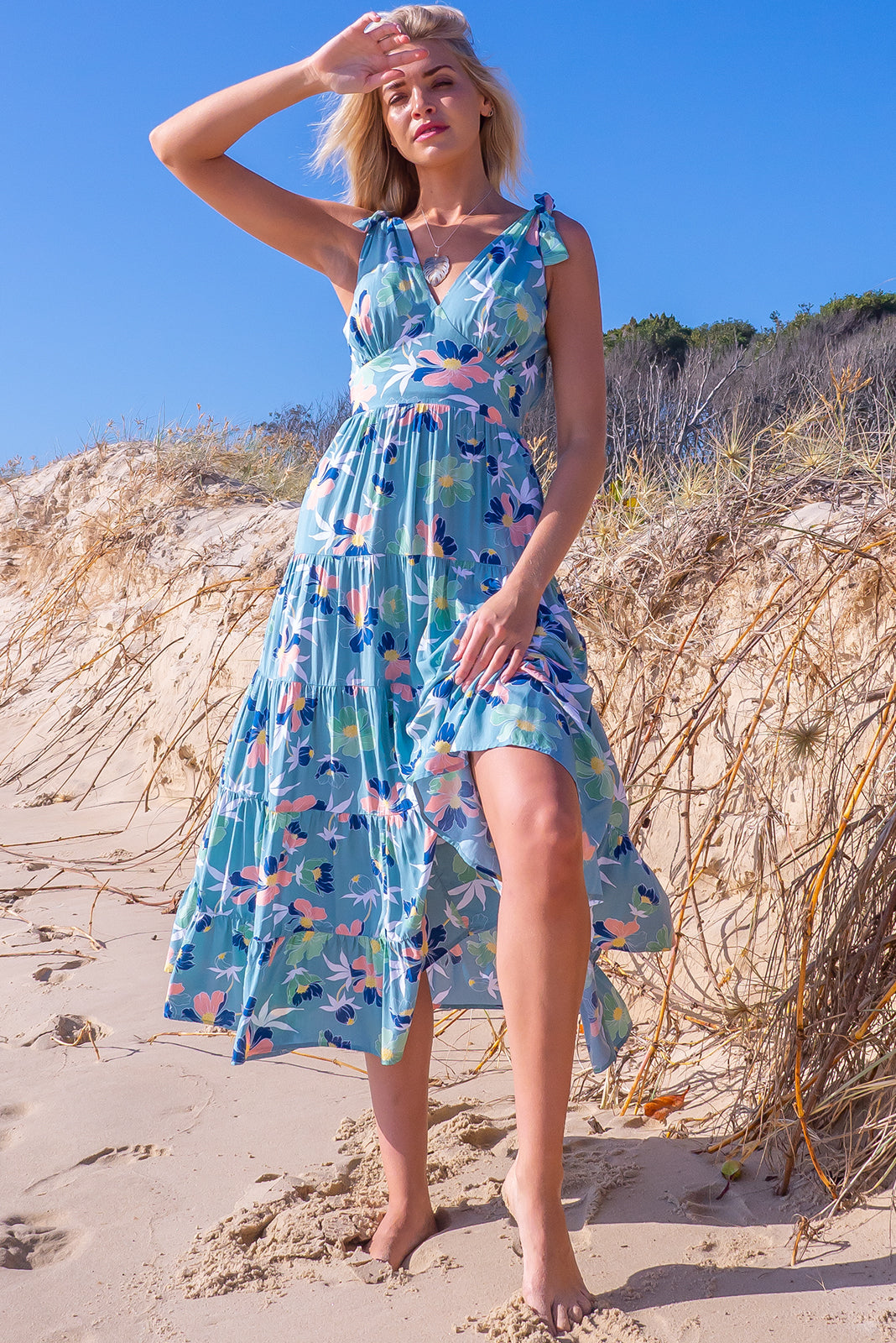 The Isla Aqua Waves Maxi Dress is ideal summer frock for cheeky weekend getaways  featuring adjustable shoulder ties, flattering front basque waist, side pockets, tiered, full skirt and 100% viscose in soft green/blue base with bold floral print.