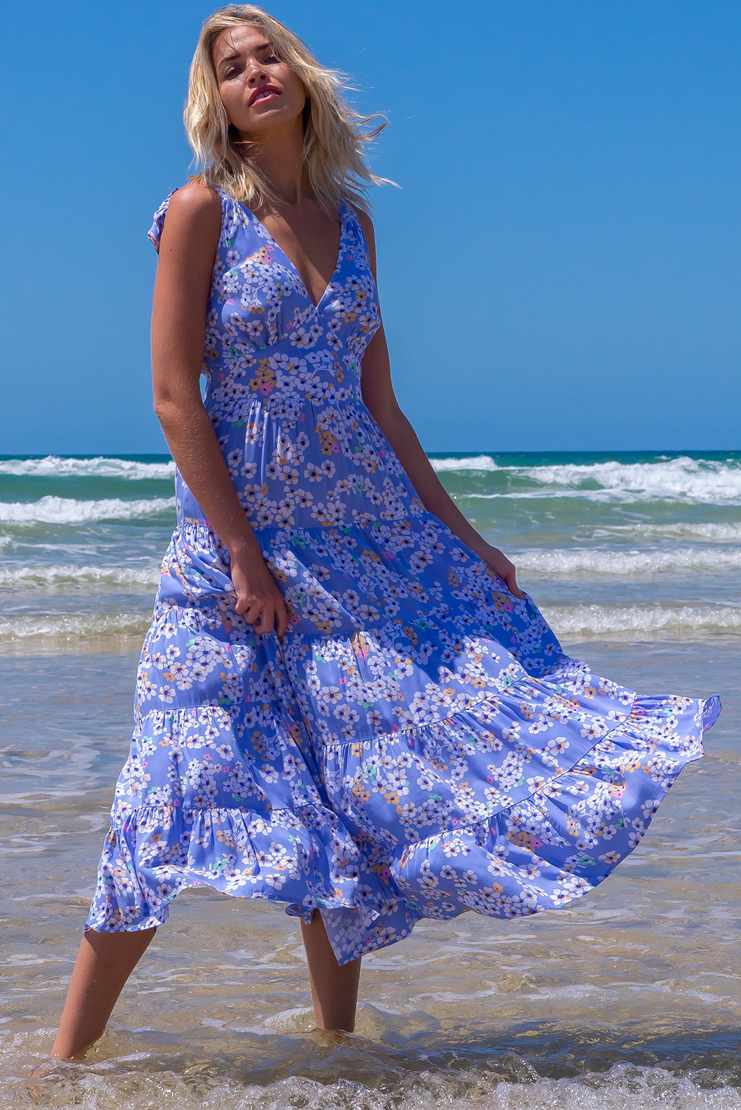 The Isla Cornflower Blue Maxi Dress features adjustable shoulder ties, shirred elasticated back waist, flattering front basque waist, side pockets, tiered, full skirt and 100% viscose in cornflower blue with floral print.