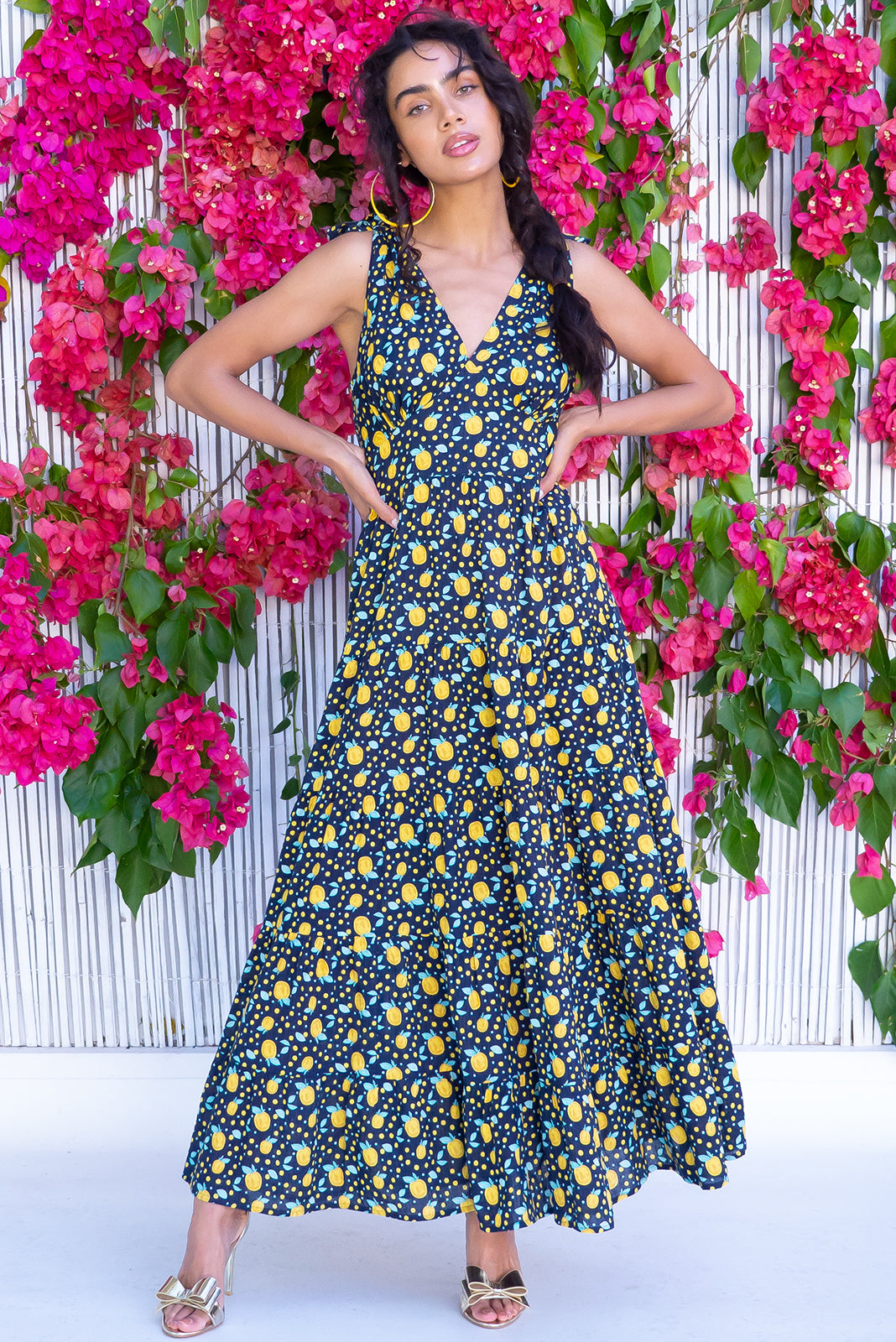 The Isla Apple Noir Maxi Dress features adjustable shoulder ties, shirred elasticated back waist, flattering front basque waist, side pockets, tiered, full skirt and Cotton/viscose blend in Ink base with yellow apple print.