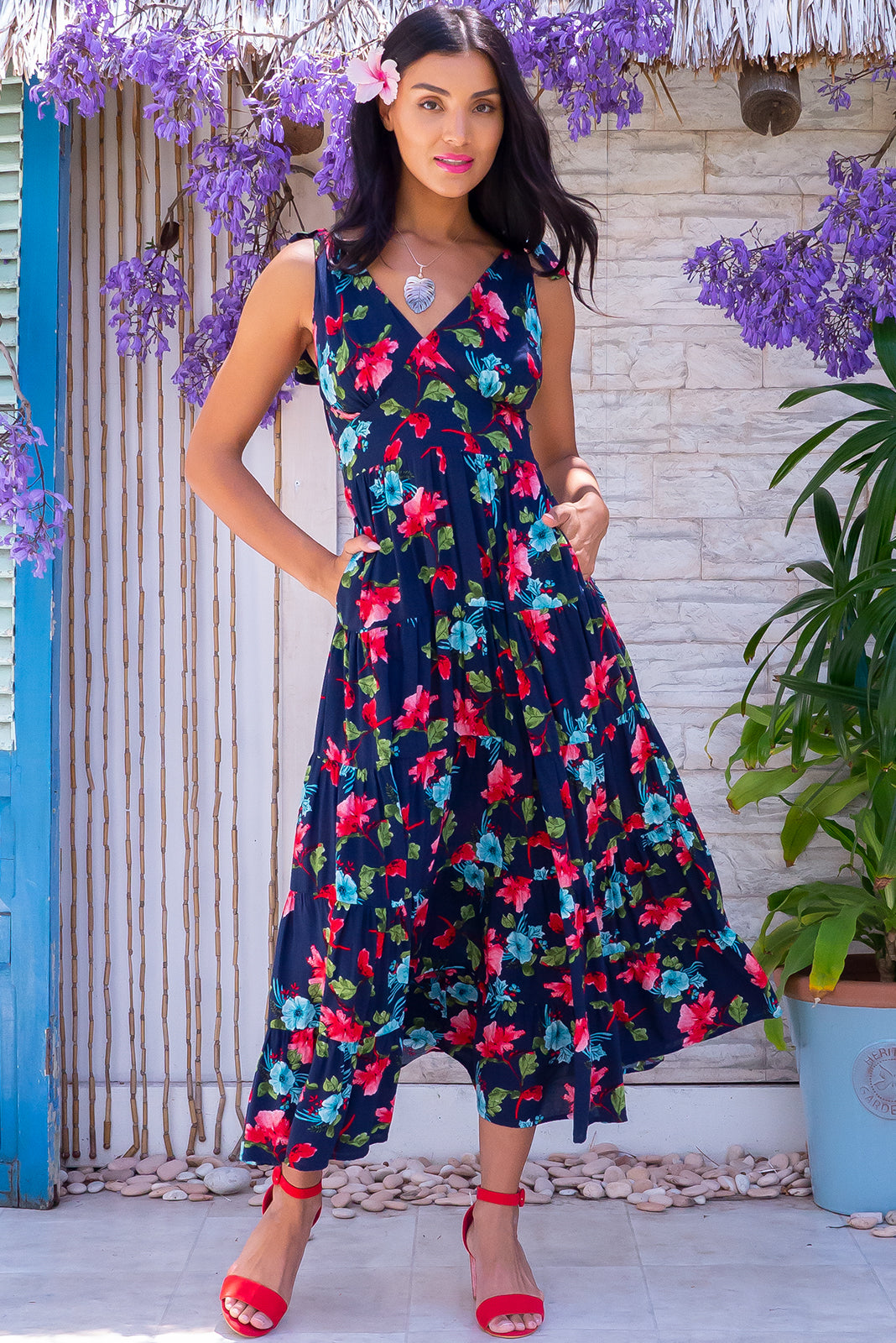 The Isla Tropic Hibiscus Maxi Dress is a tiered, full maxi skirt dress featuring adjustable shoulder ties, shirred elasticated back waist, side pockets and 100% viscose in ink base with vibrant tropical print.