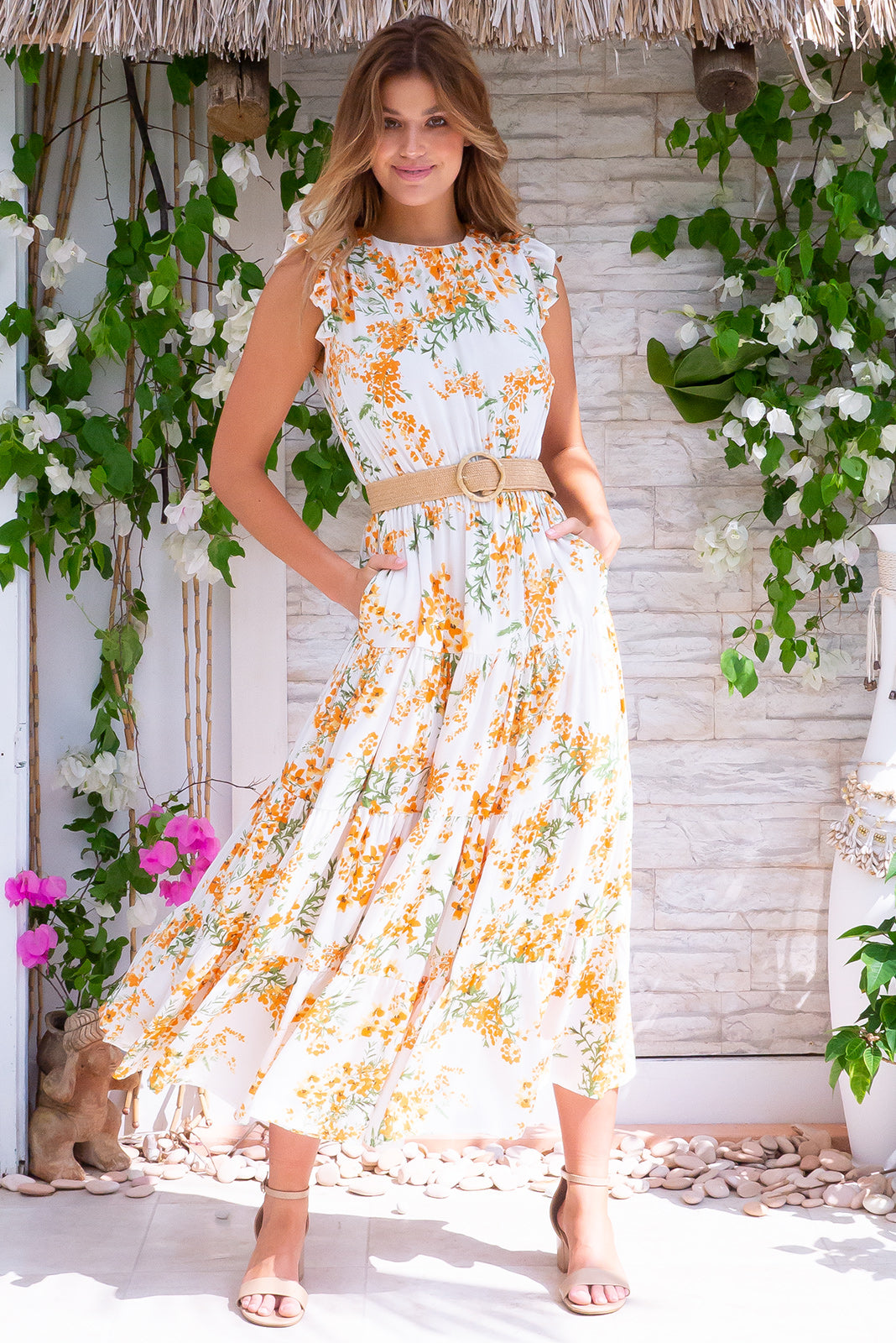 Jasmine Sunshine Floral Maxi Dress is a breezy and bright style made of woven 100% rayon, keyhole style back detail with button tab, frilled ultra short sleeves, tiered skirt, side pockets, softly elasticated waist in a white base with orange, yellow and green floral design and stretch belt with bamboo buckle included.