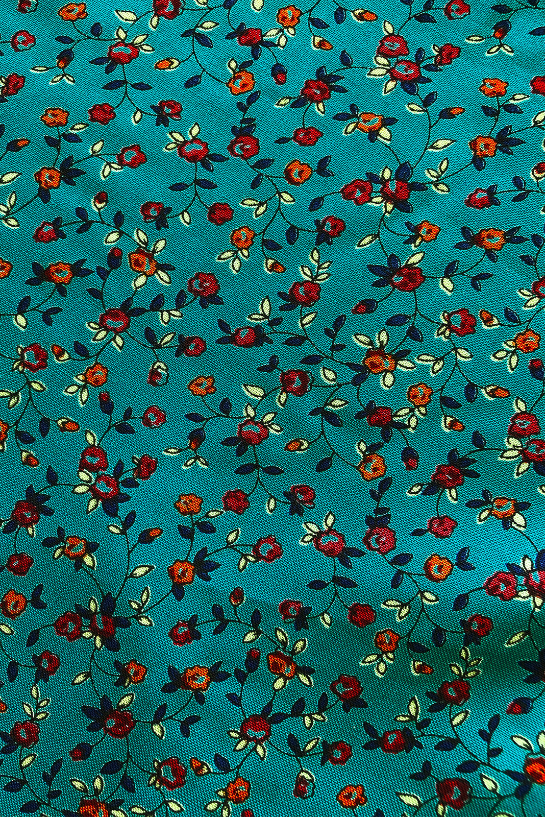 Fabric swatch, 100% woven viscose, deep teal base with petite orange, deep red, deep teal, mint floral print.
