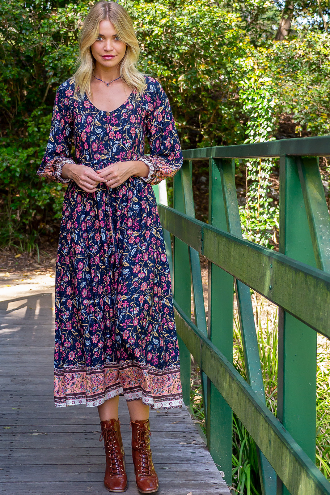 The Jaye Navy Maxi Dress features functional button front chest, elasticated sleeve cuffs, side pockets, adjustable drawstring waist and woven 100% rayon in navy base with boho floral print and border feature.