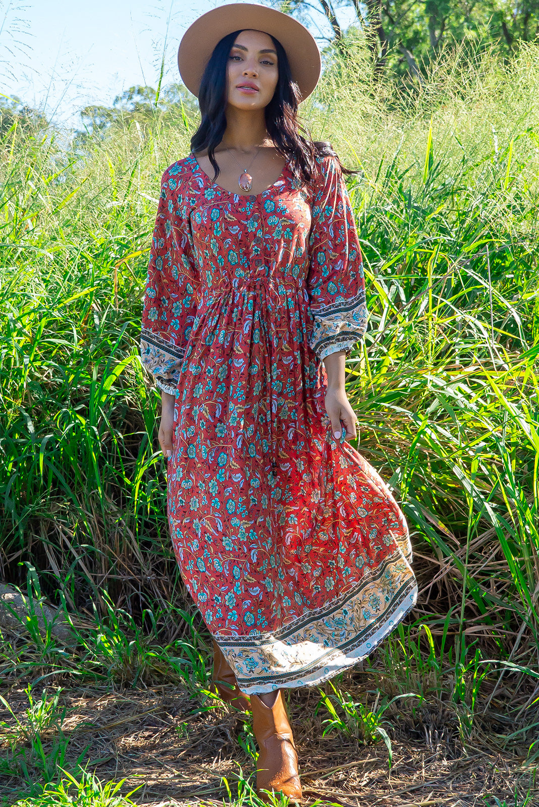 The Jaye Rusty Red Maxi Dress features functional button front chest, elasticated long sleeve, side pockets, adjustable drawstring waist, soft fit and woven 100% rayon in soft, orange red base with boho floral print and border feature.