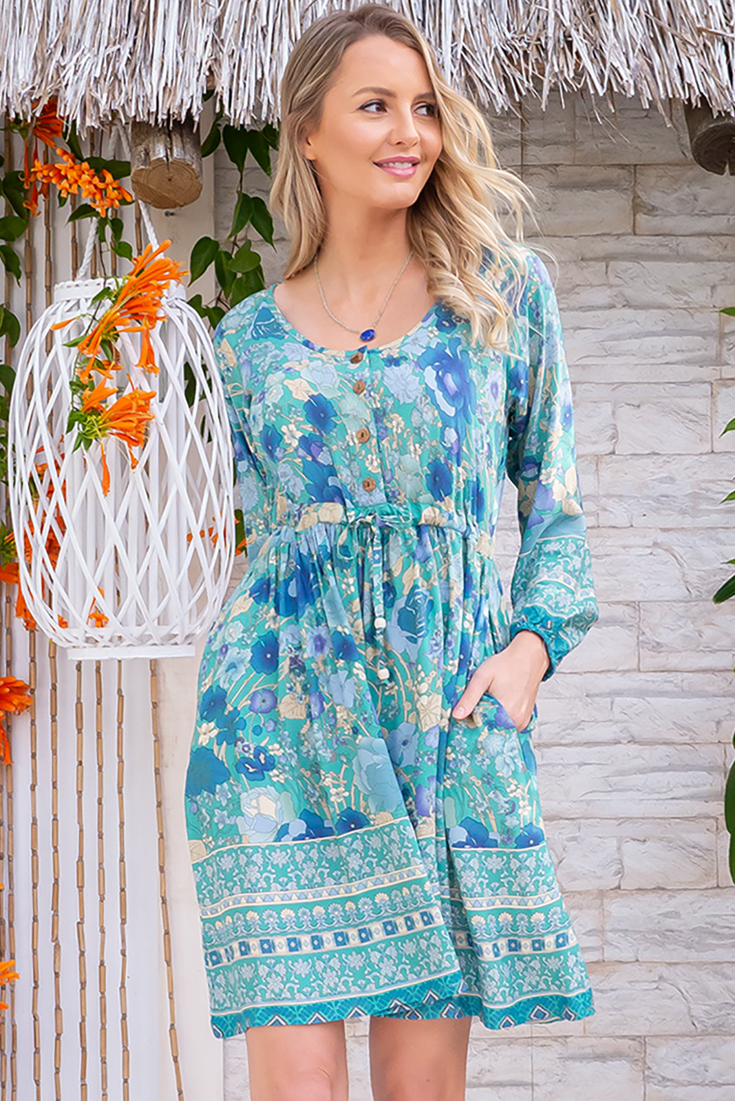 Jennifer Verte Fleur Dress is a pretty winter frock featuring functional button front to the waist, sleeve cuffs are elasticated, side pockets, adjustable drawstring waist and Woven 100% rayon in Green base with stunning blue art deco floral print, border print at hem.