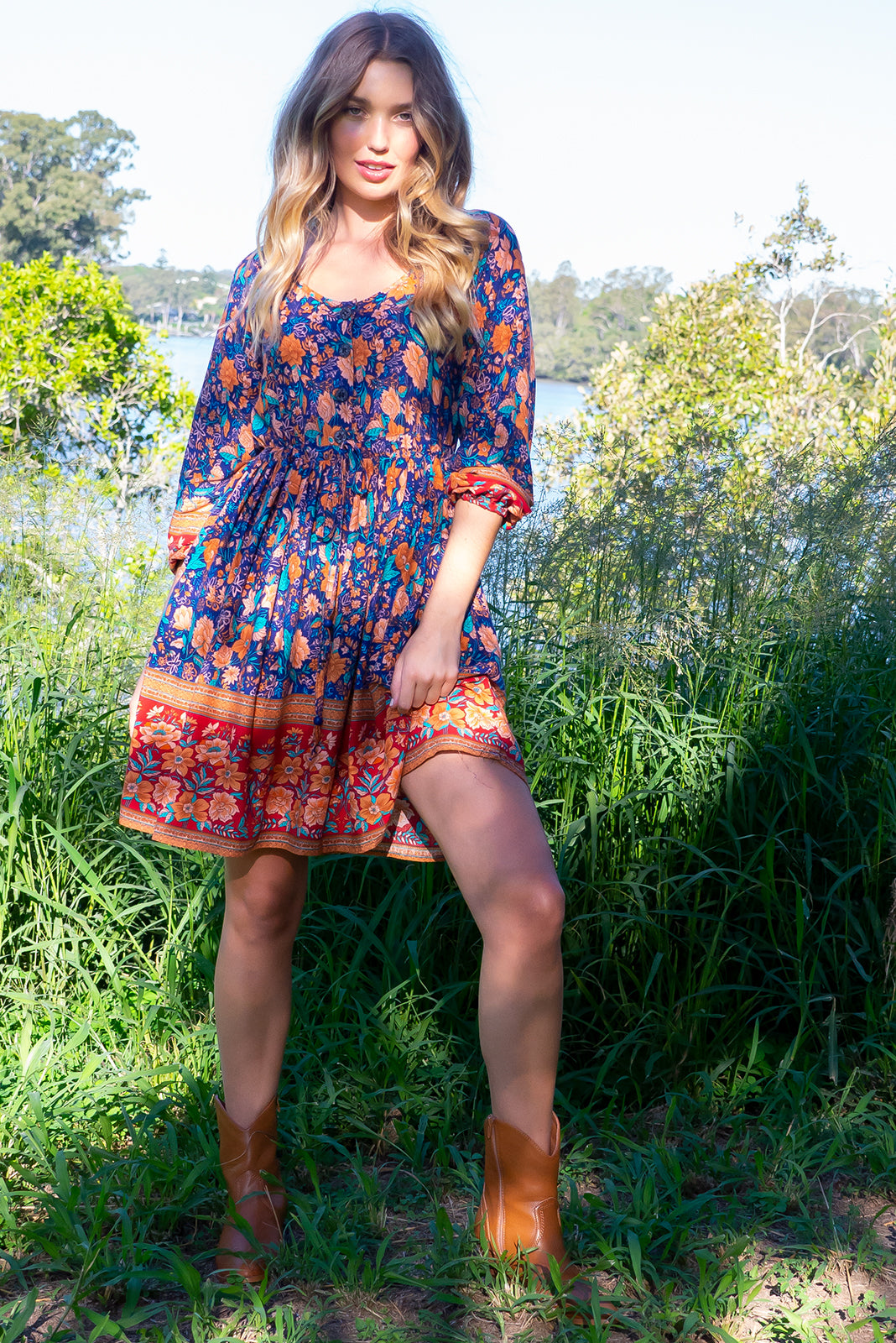 Jennifer Jos Blue Dress with a button front, long sleeve with elastic at the wrist, side pockets and a full skirt in a rust navy and ruby red bohemian border print on a 100% woven rayon chic and effortless style